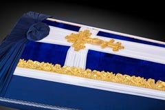 用蓝色和白色布料盖的闭合的棺材装饰用教会在灰色豪华背景的金十字架 特写镜头 免版税库存图片