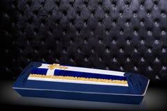 用蓝色和白色布料盖的闭合的棺材装饰用教会在灰色豪华背景的金十字架 库存照片