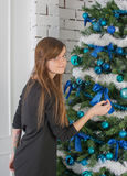 用蓝色球装饰的圣诞树的妇女 库存照片