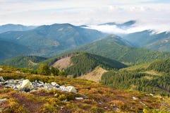 用蓬松白色云彩盖的小山 免版税库存图片