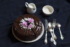 用蛋白甜饼面包屑和紫罗兰装饰的巧克力蛋糕 免版税库存图片