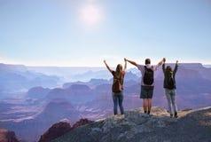 用被举的手一起享受时间的愉快的家庭在山顶部 免版税库存照片