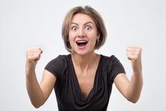 用被举的手呼喊和庆祝成功的年轻女人 图库摄影