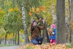 用被举的手扔有他的女儿的黄色下落的叶子的父亲在五颜六色的秋天停放得户外 库存图片