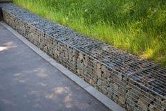 用被镀锌的金属滤网盖的操刀石头在夏天公园 库存图片