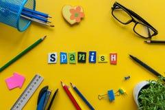 用被雕刻的信件做的西班牙语在有办公室或学校用品的,文具黄色书桌 西班牙语的概念 免版税库存照片