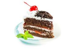 用被鞭打的奶油和cherri装饰的巧克力蛋糕可口 库存照片