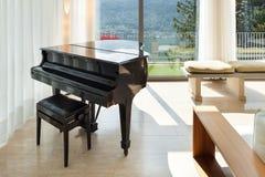 用装备的公寓,有钢琴的休息室 库存照片