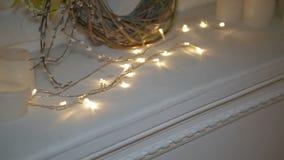 用装饰与蜡烛的Ð ¡ hristmas彩色小灯装饰的白色壁炉和圣诞节缠绕 股票录像