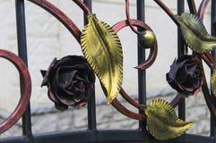 用装饰伪造的叶子装饰的金属篱芭 免版税库存照片