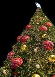用许多五颜六色和发光的装饰品装饰的巨型闪耀的圣诞树 库存照片