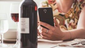 用酒app的妇女在餐馆 库存照片