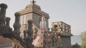 用金黄花装饰的长,令人愉快的桃红色礼服的豪华的金发女孩,小珠,在大石头大阳台  影视素材
