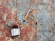 用铁锈盖的一个粗砺的金属门的难看的东西纹理,闭合对巨大的葡萄酒锁 免版税库存照片
