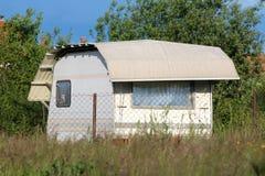 用防护尼龙板料停放在后院和盖的新的白色露营搬运车围拢与铁丝网和高草 免版税库存图片