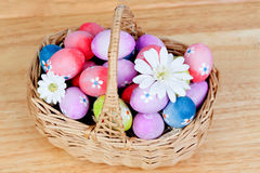 用雏菊装饰的复活节彩蛋卷起了一个篮子 免版税库存图片