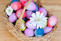 用雏菊装饰的复活节彩蛋卷起了一个篮子 免版税库存照片