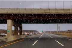 用雨小滴盖的车窗,在春季期间的多雨天气 在汽车玻璃的雨珠有被弄脏的背景 免版税库存图片