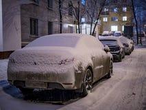 用雪停放的汽车盖在冬天 免版税库存图片