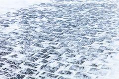 用雪和冰盖的鹅卵石路面 库存图片