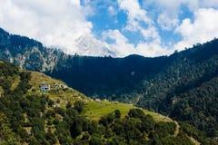 用雪和小印地安村庄报道的喜马拉雅峰顶的看法在森林里 免版税图库摄影