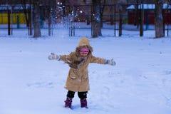 用雪盖的一个逗人喜爱的小女孩获得乐趣在冬天公园 免版税图库摄影