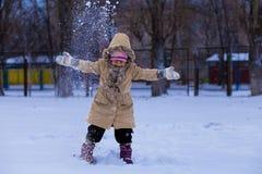 用雪盖的一个逗人喜爱的小女孩获得乐趣在冬天公园 图库摄影