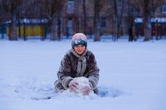 用雪盖的一个逗人喜爱的小女孩获得乐趣在冬天 图库摄影