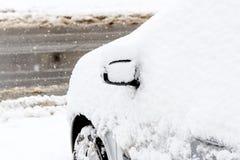 用雪盖的一辆汽车在风暴以后 免版税库存照片