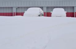 用雪盖的两辆汽车 免版税库存图片