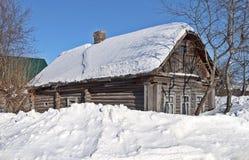 用雪盖的老日志小屋 库存图片
