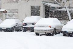 用雪盖的停放的汽车在冬天 免版税库存照片