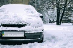 用雪盖的停放的汽车-雪风暴,在以后的汽车大雪,在汽车的很多雪,汽车在多雪的围场,正面图 免版税库存照片