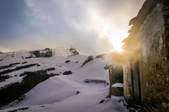 用雪盖的山的老房子 库存图片