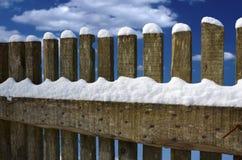 用雪盖的木篱芭在多云蓝天之前 免版税库存照片