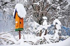 用雪盖的橙色鸟舍 库存图片