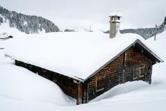 用雪盖的瑞士山中的牧人小屋 免版税库存图片