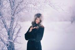 用雪盖的美丽的愉快的笑的少妇佩带的冬天帽子手套剥落 免版税库存图片