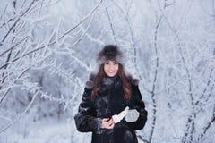 用雪盖的美丽的愉快的笑的少妇佩带的冬天帽子手套剥落 免版税库存照片