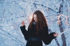 用雪盖的美丽的愉快的笑的少妇佩带的冬天帽子手套剥落 库存图片