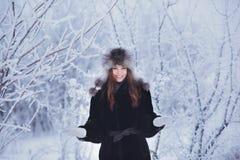 用雪盖的美丽的愉快的笑的少妇佩带的冬天帽子手套剥落 图库摄影