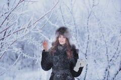 用雪盖的美丽的愉快的笑的少妇佩带的冬天帽子手套剥落 免版税图库摄影