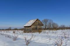 用雪盖的老被放弃的农厂房子风景在一个冷淡的冬天 免版税库存图片