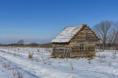 用雪盖的老被放弃的农厂房子风景在一个冷淡的冬天 免版税库存照片