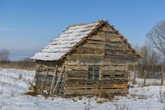 用雪盖的老被放弃的农厂房子风景在一个冷淡的冬天 库存图片