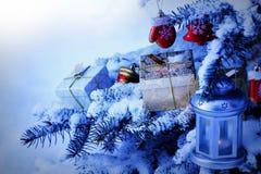用雪盖的自然杉树 垂悬在杉树分支的圣诞节装饰 放置在分支的礼物盒 免版税图库摄影