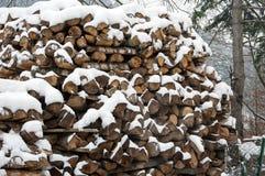 用雪盖的被堆积的木头 背景 免版税库存图片