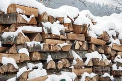 用雪盖的被堆积的木头 背景 图库摄影