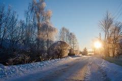 用雪盖的路在日落的俄国村庄冬天 免版税库存图片