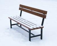 用雪盖的长木凳-冬时圣诞节 库存图片